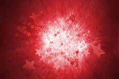 Structured star. A structured, red star, exploding with various other stars, and a motion blurred, white light in the background Stock Photos