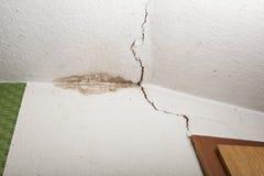 Structurele schade op plafond, vorm in hoek, barst in plafond stock afbeeldingen