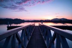 Structuur van de pier die tot de mooie zonsopganggloed leiden royalty-vrije stock afbeelding