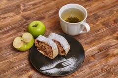 Strudel της Apple με τη ζάχαρη τήξης και σταφίδες στο μαύρο πιάτο Στοκ φωτογραφίες με δικαίωμα ελεύθερης χρήσης