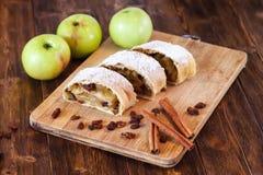 Strudel της Apple με τη ζάχαρη τήξης, ραβδιά κανέλας, ξύλινο υπόβαθρο Στοκ φωτογραφία με δικαίωμα ελεύθερης χρήσης
