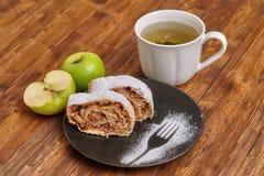 Strudel της Apple με τη ζάχαρη τήξης στο μαύρο πιάτο, ξύλινο υπόβαθρο Στοκ Φωτογραφία