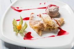 Strudel της Apple με το παγωτό, το ριβήσιο ακρωτηρίων και τα φρούτα που διαδίδονται στο άσπρο πιάτο Στοκ Εικόνα