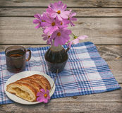 Strudel with apples and a cup of tea next to a bouquet of cosmos Royalty Free Stock Photography