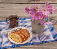 Strudel with apples and a cup of tea next to a bouquet of cosmos Stock Image