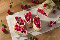 Strudel with cherry on paper napkin. Homemade cherry strudel on paper napkin Royalty Free Stock Image