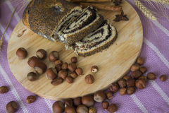 Strudel del papavero sul piatto di legno con le nocciole immagini stock