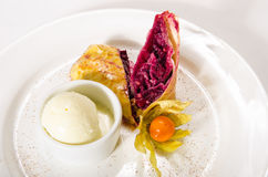 Strudel of frozen puff pastry with cherry on white plate royalty free stock photos