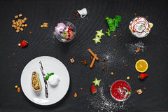Strudel with ice cream, fruit with cream, panacota on a black ba. A set of desserts, strudel with ice cream, fruits with cream, panacota on a black background royalty free stock photography