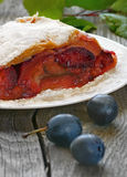 Strudel with plums. On a white plate on a wooden table Stock Photography