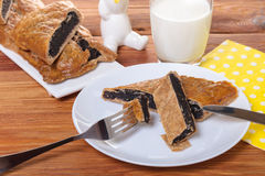 Strudel with poppy in a plate. On wooden background Stock Images