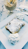 Strudel with powdered sugar and cream at cafe. stock photos
