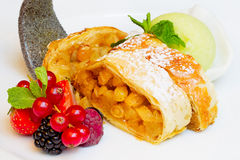 Strudel with raisins, fresh berries and ice cream. Slices of strudel with raisins and apples, sprinkle with powdered sugar on a white plate with fresh berries Stock Photo