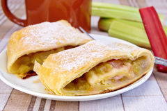Strudel with rhubarb and mug on linen tablecloth Stock Photo