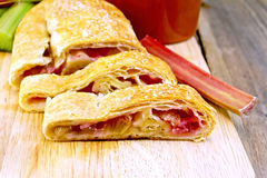 Strudel with rhubarb and mug on wooden board Royalty Free Stock Photos