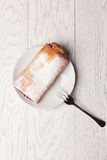 Strudel on table. Strudel on plate with fork on wooden table Stock Images