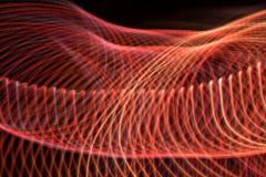 Strudel und Wellen von roten Lichtern mit irgendeinem Blau mit einem schwarzen Hintergrund stockfotografie