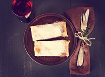 Strudel and wine. Strudel, Apple strudel (pie) with wine on dark background Royalty Free Stock Photography