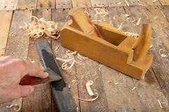 Strug in een oude timmerwerkworkshop Het scherpen en behoud van het oude timmerwerkhulpmiddel stock afbeelding