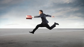 Struggle. Young businessman running in a desert Royalty Free Stock Photography