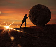 Struggle and determination. Man pushes a boulder uphill at sunset Royalty Free Stock Images