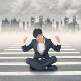 Struggle at modern city. Young Asian businessman sit on ground and feel relax or struggle at modern city Stock Image