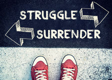 Struggle and surrender. Student standing above the sign surrender and struggle Royalty Free Stock Photography