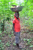 STRUGGLE TOGETHER AGAINST CHILD LABOUR. African child with a container of food products on the head by nature, deprived of her childhood and studied for its Stock Photo