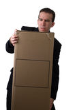 Struggling Businessman. A young businessman struggling to lift a box with your text on it Royalty Free Stock Images