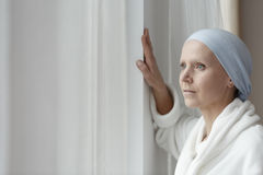 Struggling with cancer alone. Depressed woman with blue scarf struggling with breast cancer alone royalty free stock image