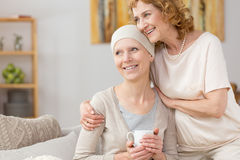 Struggling with illness. Happy women with scarf struggling with illness with her mom`s help Royalty Free Stock Photography