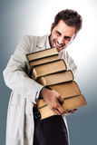 Struggling medical student. A young and handsome doctor or medical student carrying a pile of ancient book Stock Images