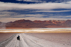 Struggling in nowhere. Woman cyclist struggling and pushing her bike on the sandy corrugated road in Altiplano in Bolivia Royalty Free Stock Image