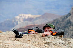 Struggling Photographer. Photographer struggling to climb on the top of a high mountain Stock Photography