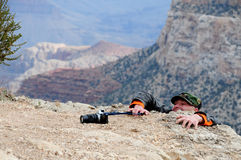 Struggling photographer. A view of a photographer clinging to the side of a steep canyon, trying to reach his camera or photographic equipment at the top Stock Image