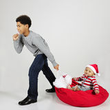 Struggling Pullerl, Happy Rider. An elementary boy strubbling to give his baby brother a ride across the floor on Santa's sack.  On a gray background Stock Photos