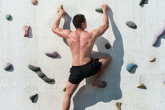 Struggling To Reach Handhold On Climbing Wall Stock Images