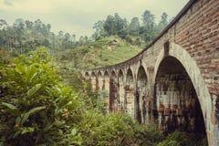 Struktur av den historiska bron för nio bågar i härligt tropiskt landskap med av den gröna skogen och byn Arkivfoto