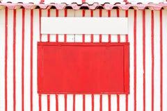 Strukturierte rote Wand mit Feld und geschlossenem Fenster. Lizenzfreies Stockfoto