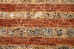 Strukturierter Hintergrund der mittelalterlichen Wand des Ziegelsteines und des Steins stockfotos