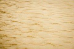 Strukturierter Hintergrund des weichen Sandes. Gelbe Farbe. Lizenzfreie Stockfotografie