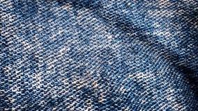 Strukturiertes blaues Flattern des Denimgewebes Lebhafte Bewegung des Segeltuches Hintergrundanimation von den Jeans, die in flat stockbilder