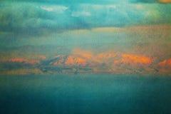Strukturiertes Weinlesebild von glühenden Bergen über Meer Stockfotografie