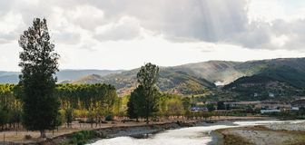 Struma River in Bulgaria. Picturesque landscape with mountain slope overgrown with trees, village with red roofs and the Struma River, Bulgaria royalty free stock photography