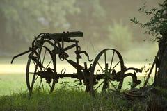 Strumentazione antica dell'azienda agricola in nebbia Immagini Stock