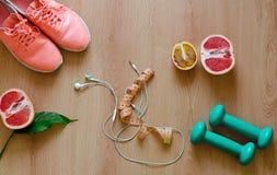 Strumentazione di forma fisica Scarpe da tennis ed alimento salutare su fondo di legno Fotografia Stock
