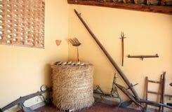 Strumenti antichi dell'azienda agricola e parete gialla Fotografia Stock