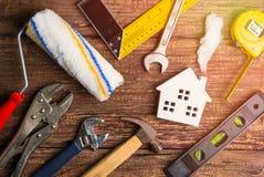 Strumenti bianchi di legno del giocattolo e della costruzione della casa sul backgrou di legno Fotografie Stock