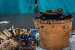 Strumenti del batik, smussare e cera calda sopra la tavola di legno per batik che elabora con la parete blu come foto del fondo c fotografie stock
