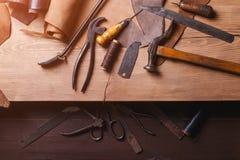 Strumenti del calzolaio in officina sulla tavola di legno Vista superiore Immagini Stock